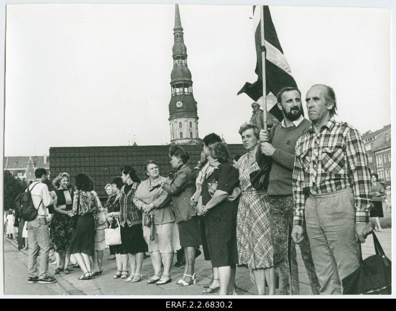 Baltic chain on the territory of Latvia. People waving flags. The tower of the Riga Peetri Church looks behind