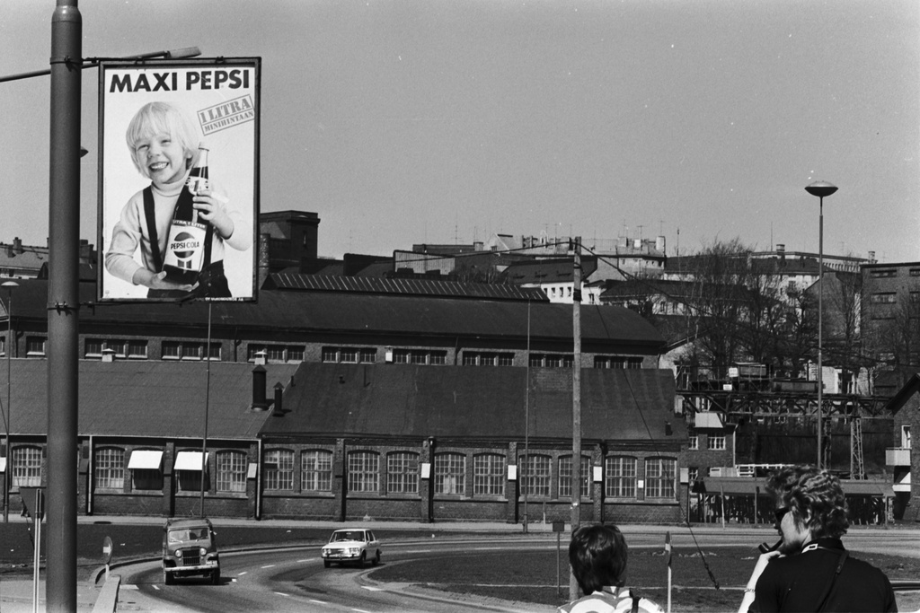 Sörnish beachway 9-11. View from the Hakaniemi bridge towards the Sörnäisten beaches. On the left Maxi Pepsi beverage advertisement in the lamp. Behind the industrial buildings of Oy Wärtsilän Ab, former Machine and Siltarakennus Oy.