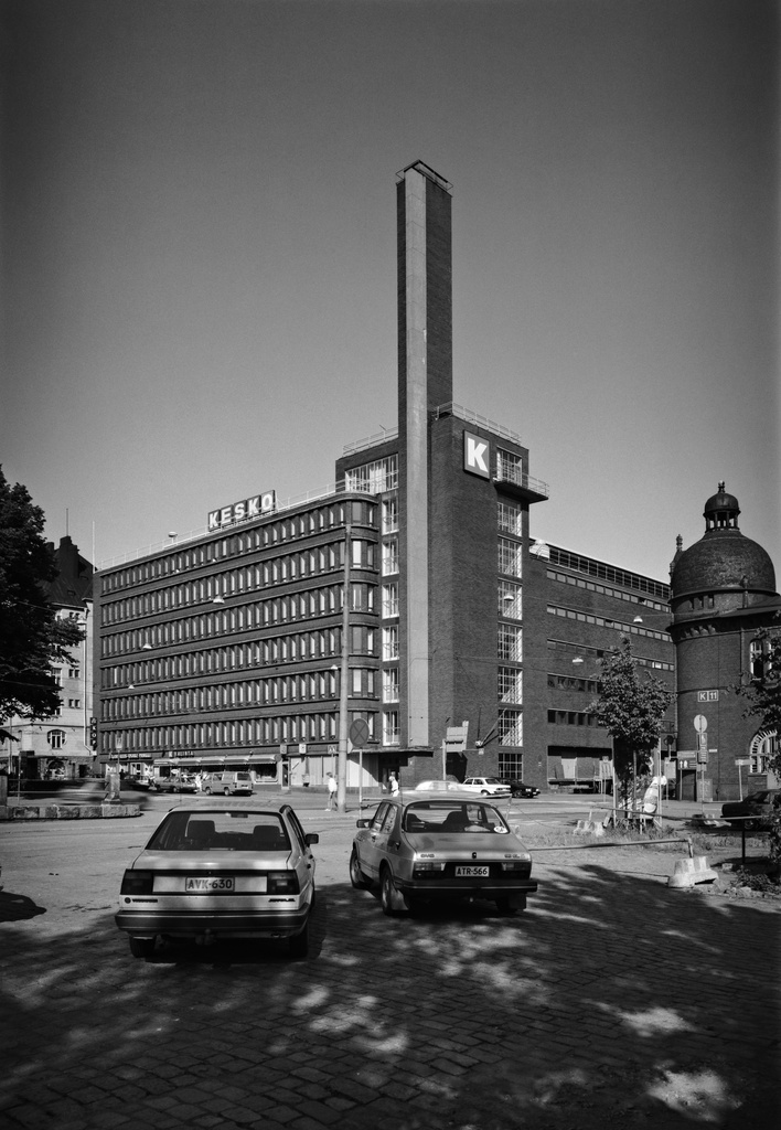 Kesko Headquarters Satamakatu 3 - Kanavakatu 1. On the right edge there is a corner from Satamakatu 1, the architect Gustaf Nyström drawing Katajanoka customs and packing room. In the photo in the front area, two passenger cars are parked in the shadow of newspaper trees.