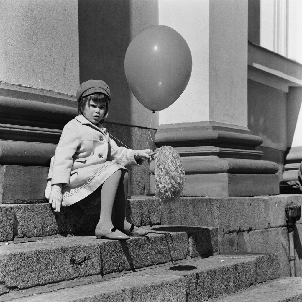 A little girl sits on the day of liberty with a balloon and a waffle in her hand on the steps of the Judicial Church.