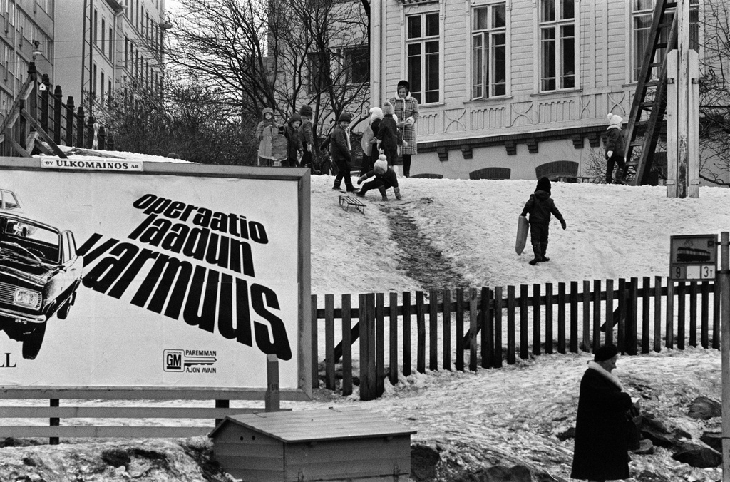 Vauxhall car advertising (Operation Quality Assurance) in the corner of Porthanin Street and Siltasaarenkadu. On the background children counting hills in the wooden house, the Stockholm nursery garden. Spring 1970.