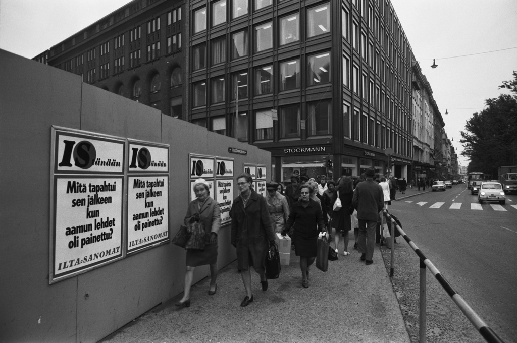 Northern Esplanadi 41, 39. Conversation 1a. Pedestrians at the building of Stockmann's new building in the corner of Northesplanad and Keskus street. Advertisement of the building site in the courtyard of Ilta-Sanomien: What happened after the newspapers were printed in the morning?.