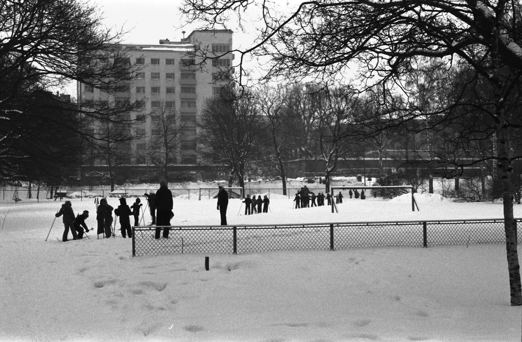 Kaisaniemen park. The children and adults of Vironniemi babysitter in the snow in Kaisaniemenpark are preparing for departure for the ski park. Behind the Unioninkatu 39 apartment building and the corner of Unioninkatu 37.