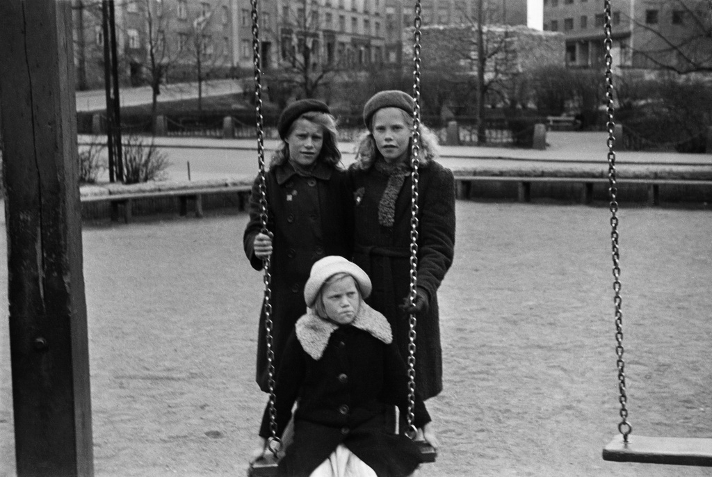 Three girls in the Bear Park (ent. Agricolan Park, one sits in a swing. Behind Fleminginkatu and Agricolankatu.