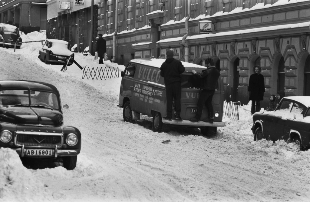 Sea duty roof 25. Two men standing in weight behind the van with snow on the Meritulli Street. View from Liisankadu towards Kruununhaan street.