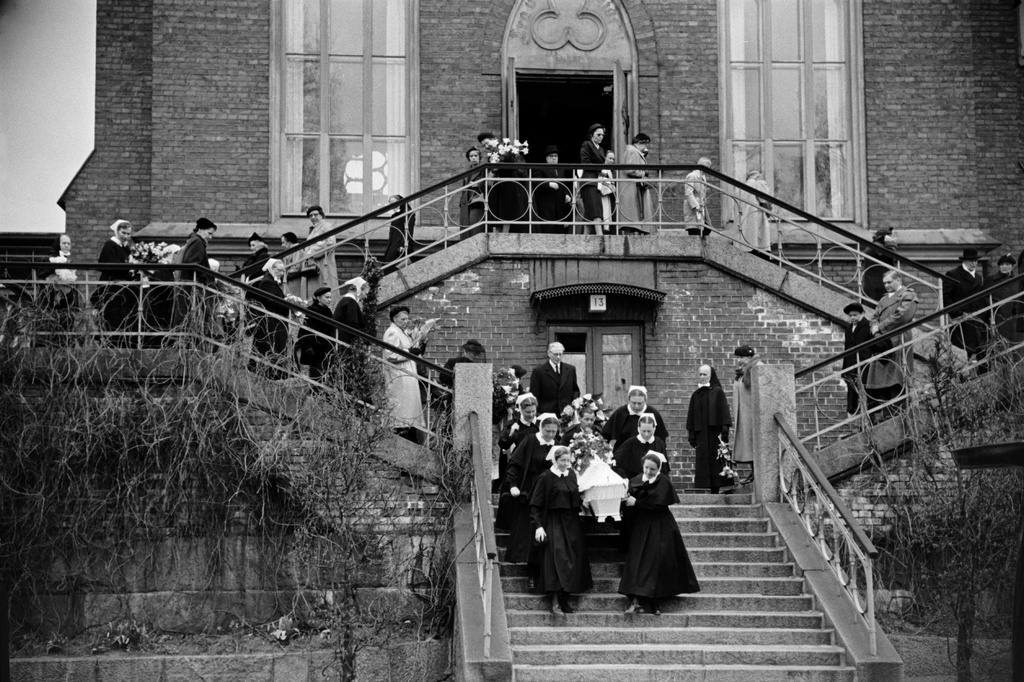 The church of the Helsinki Diaconi institute, the funeral of Ester Svensson, the funeral. The Diagons carry the ark down the stairs towards the car.