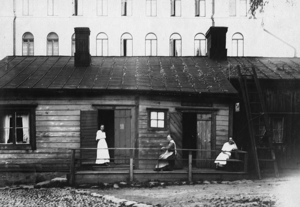 Women in the family of Kuusela on the chastise of the home house in New Country 26. On the right Selma Kuusela, in the middle of mother Charlotta Kuusela and on the left Martta Kuusela. Behind New Country Street 23 stone houses.