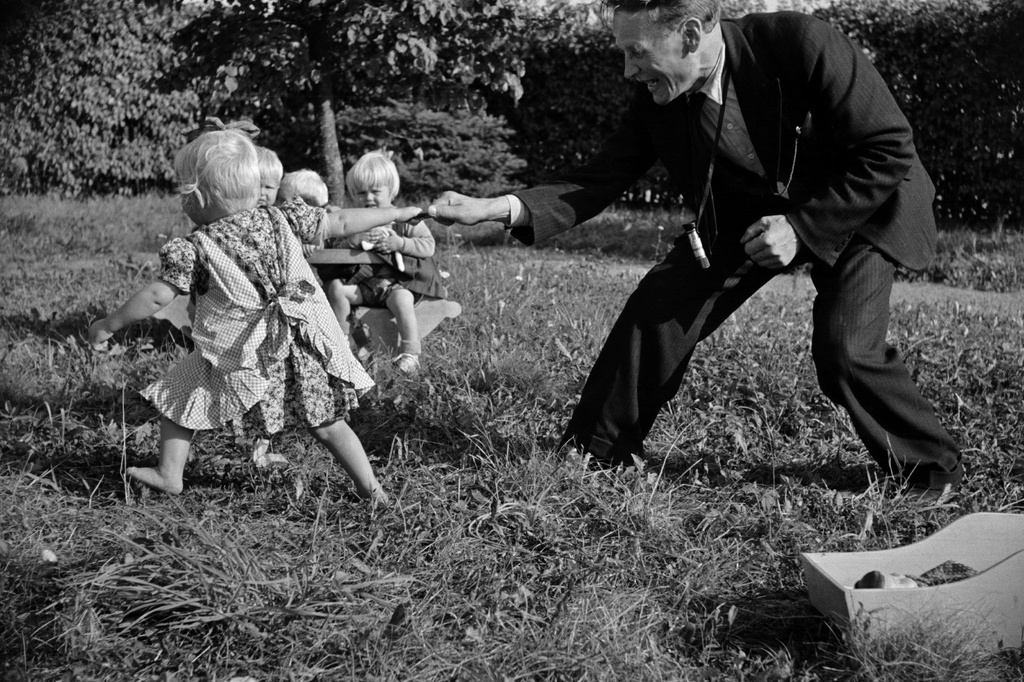 The girl plays with the photographer Väinö Kannisto in Aunela's children's home yard.
