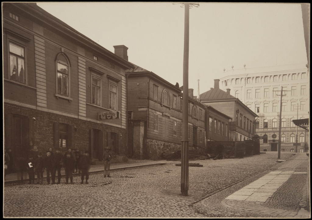 Rikhardinkatu 2, 4, behind the Height Mount tyre 30. In front of the left group of children, in Rikhardinkatu 2, a. Helenius advertisement sign and offices.