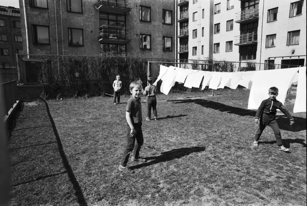 Fourth line 24. Long view to northwest Third Line - Castréninkatu - Fourth Line - Suonionkatu streets surrounded by the block. In front of the sons playing football Fourth Line in the 24 lawn garden with a whitewasher flaking with a rod drying. Background Fourth Line 26.