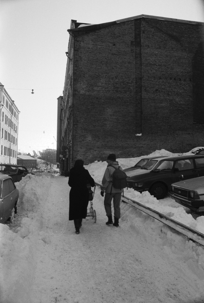 Sea duty roof. Mother (Etta Harvilahti) pushing children's trailers with snow on Meritulli Street. On the right cars Meritullinkatu 8 in unbuilt building. Behind the bridge end of the 6th house of the Meritullinkatu.