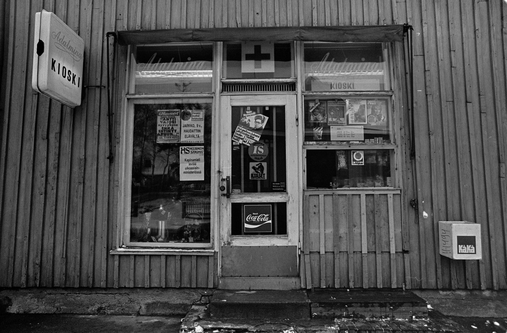 Kioski in the wooden building of Adalmina in Toukola. Advertisements and press blows are attached to the windows of the kiosk. Above the kiosk service lounge, there are leafs for sale.