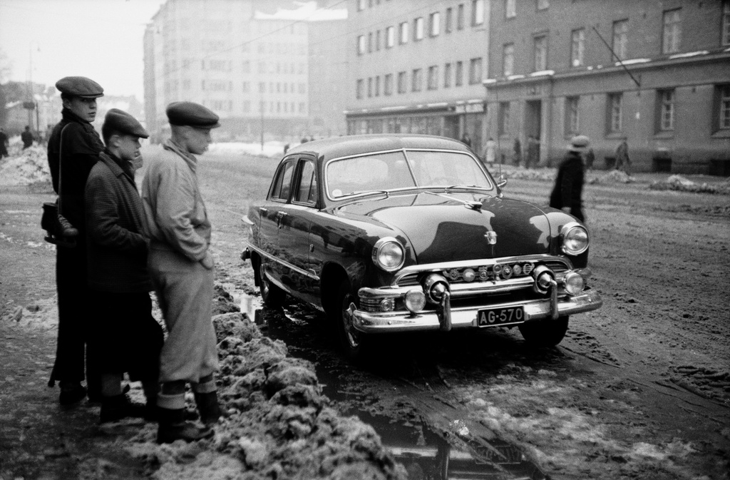 Three boys watching a car parked in front of Helsinginkatu 9 (black quadrilateral Ford sedan, etc.) 1951). Behind the Harjutori and Helsinginkatu 6, 10.
