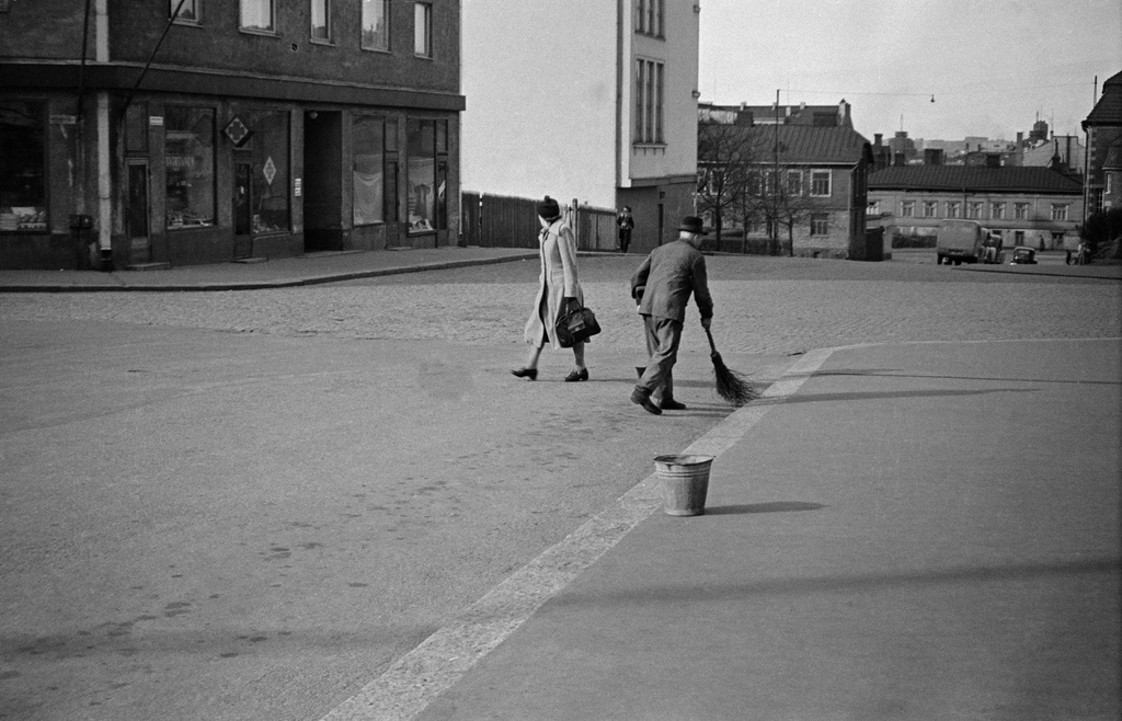 From the crossing of Agricolankadu and Torkkelinkatu, a view to the lunch gun along Porthaninkatua. In front of the housekeeper Heinonen, with cutting tools. On the left, Porthaninkatu 17 (Bruno Virtanen), 15 (=Kallio Joint School, nyk. High school of the rock, 13. On the right hand, Kallio library. The buildings of the Fifth Line (6,8) are visible on the back.