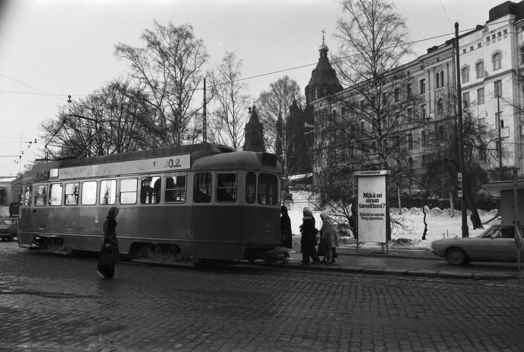 Katajanokka, Satamakatu. Passengers on a narrow stop height rising to the 5 tram number 348 stops on the side of the Katajanoka park (now Tove Jansson Park). Behind the Money Pajankatu and the Cathedral of Uspensk. In the third-screen foreign advertisement, the Nordic United States Bank's advertisement.