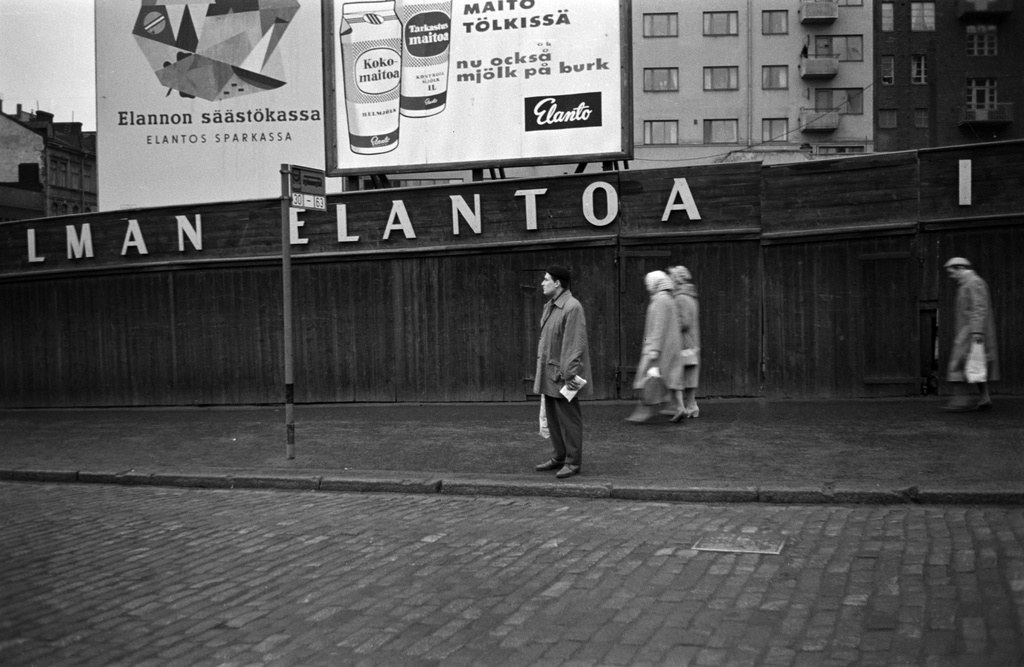 Hämeentie 16. A man on bus stops and pedestrians on the street. On the back of the boards and Elannon's savings bag, as well as the advertisements for milk sold on the flat. Picture from 1958, when dairy bags came into use. Hämeentie 16 empty plot. Behind it Fourth Line 3.