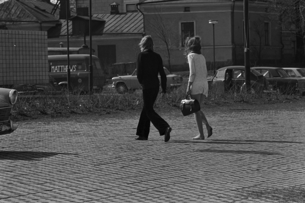 Next line 2. A black-dressed man and a white mini-dressed woman walking in the spring wind in the area stoned at the corner of the Helsinki City Theatre on the side of the first line. Behind Hedvig Sofiahemmet building.