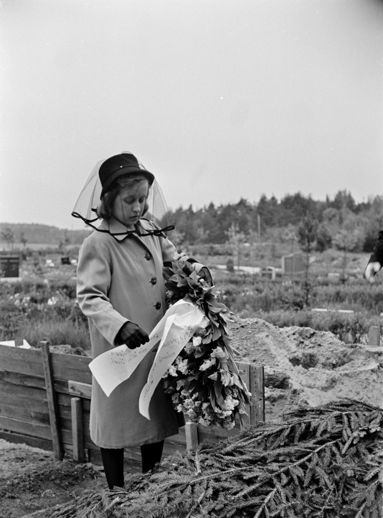 Northern graveyard (= Malmi graveyard), funeral. A sad woman puts a contest on the grave.