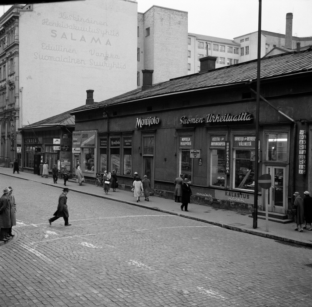 Mikonkatu 8 (in 1960 destroyed building). The property operates before the house was dismantled Karjanlahti Oy, photography movement Monifoto, bartender movement, Finnish Sports Theatre, Sorea toilet and Aikala-kellosnliike. Behind the left there is Mikonkatu 6. Today the property is located in 1961 graduated from the Timehouse.
