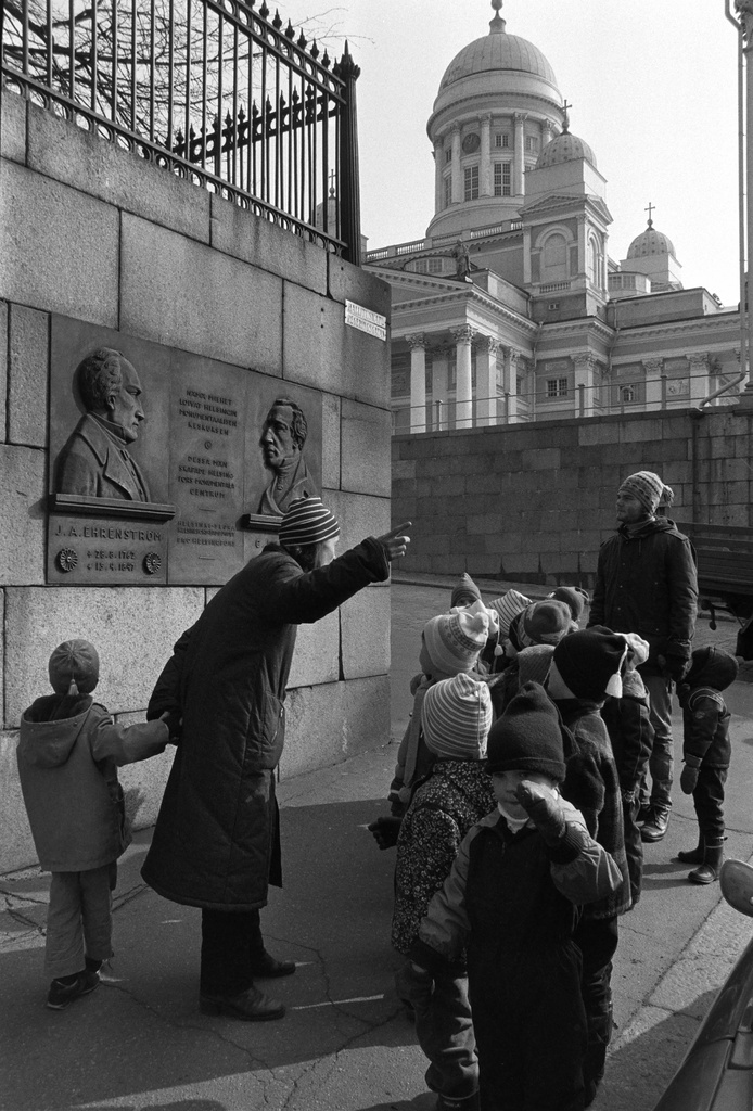 Yliopistonkatu. The children of Vironniemi Children's House at the Hallitus Street (Yliopiston Street) in the corner of Union Street in front of Ehrenström and Engel's pronssic memorial relief designed by the photographer Felix Nylund. Children's garden teacher Kirsti Hakkola presents children the buildings of the Helsinki monumental centre. Visiting the city was related to the Viihty Environment project implemented in the nursery in spring.