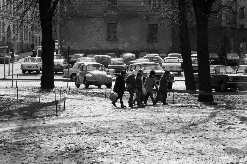 Schoolchildren walking in Säätitalo park. Behind parking cars in the unbuilt building of Kirkkokatu 12. Spring 1971.