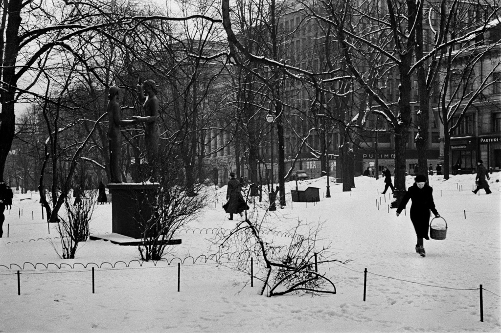 In winter, in front of the left Zacharias Topelus, the monument of Taru and True (Gunnar Finne, 1932), around the pedestrians. Behind the southern Esplanade Street (=Eteläesplanadi) 12-20.