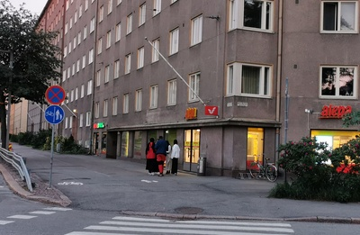 Manterheimintie 152. - Sixtie 2. Livelihood shop, meat shop, Helsinki stock bank. In front of the postal car and the postal employee are going to empty the postal box. rephoto
