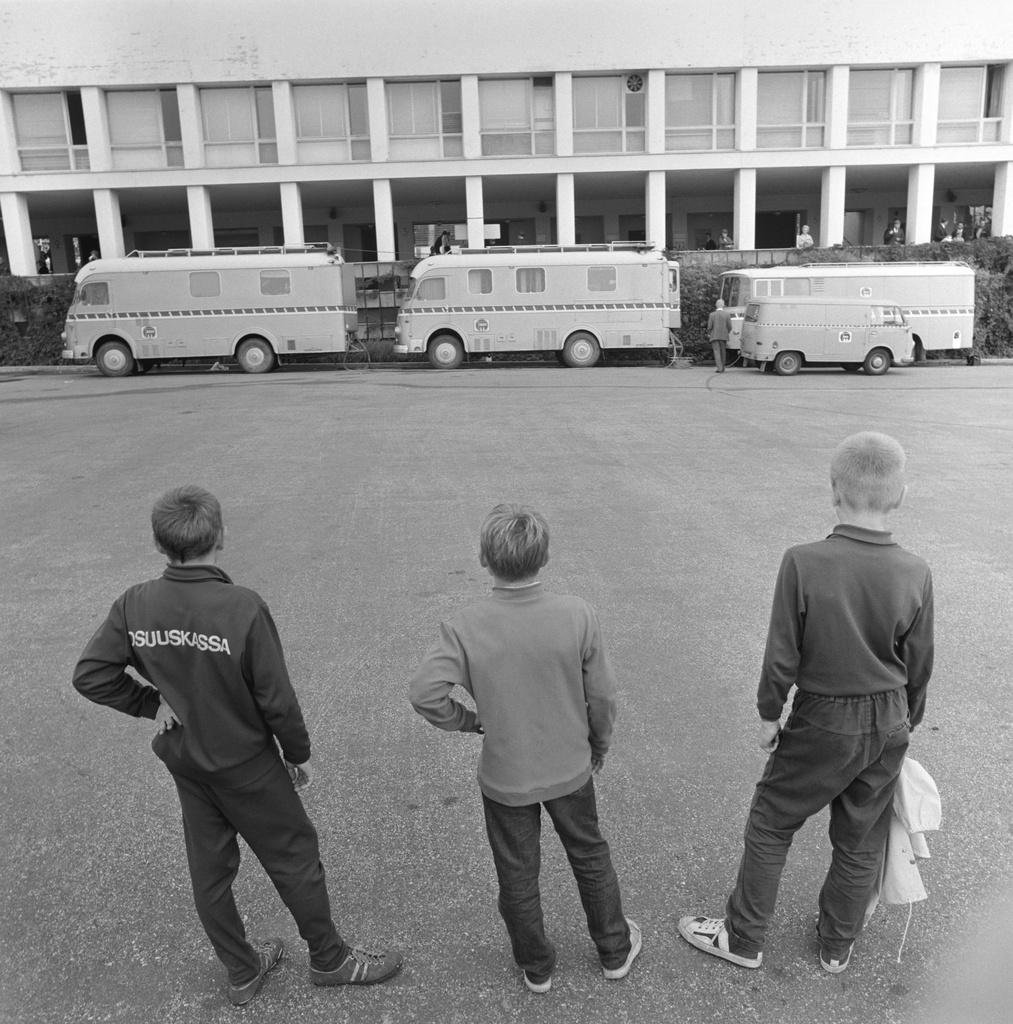 Three boys watch at television and radio broadcasting vehicles