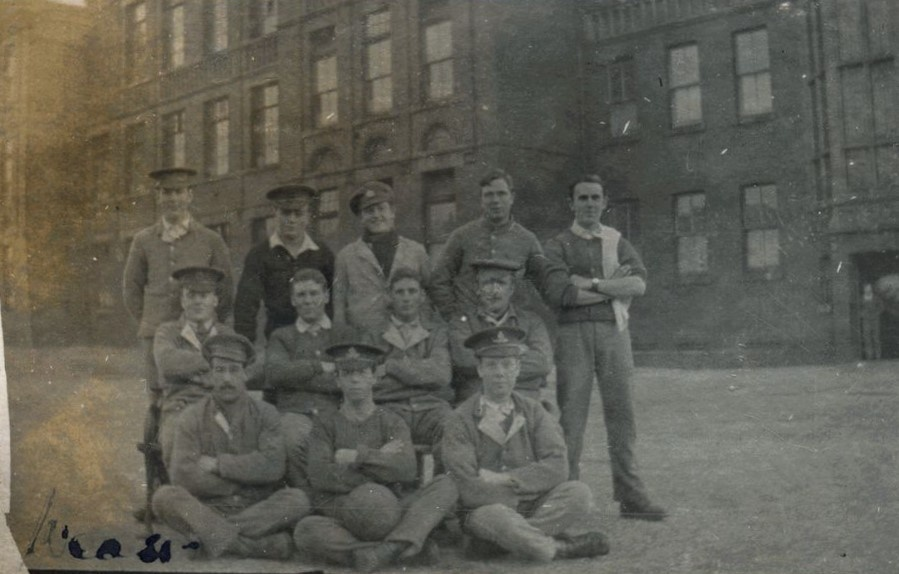 Group of men in First World War military uniform posed outside building, three seated on the ground, four on chairs and five standing. The middle man seated on the ground has a football on his lap.