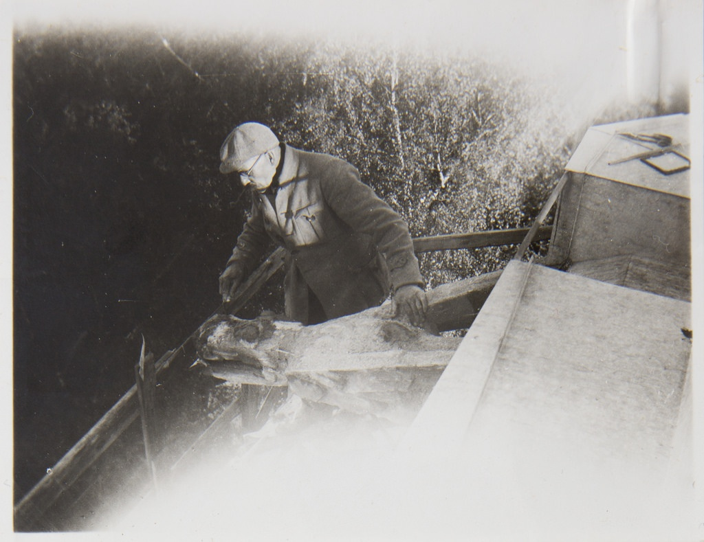 Akseli Gallen-Kallela on the tower of Tarvaspää working on a dragon-shaped gargoyle, 1927; photograph 4.