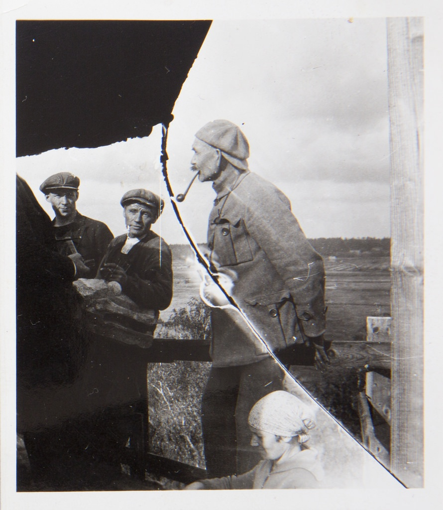 Akseli Gallen-Kallela with a pipe in his mouth, sculptor Alpo Sailo (the hand with a hammer on the left) and workers on the tower of Tarvaspää, 1927.