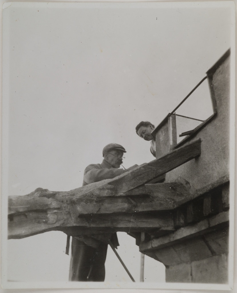 Akseli Gallen-Kallela on the tower of Tarvaspää working on a dragon-shaped gargoyle with his wife Mary watching, 1927.